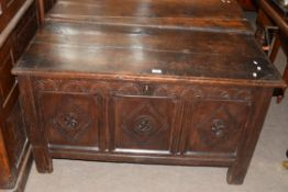18th century oak coffer with three panelled front, decorated with carved detail and fitted with