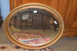 20th century oval bevelled wall mirror set in a gilt finish frame