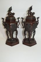 Two Oriental metal censers on shaped bases, the finials with dog of Fo and with decoration in relief