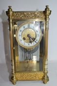 French gilt brass and four glass mounted clock, the circular white enamel face with Arabic