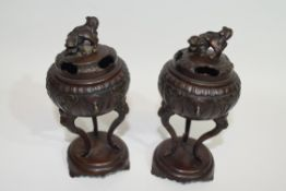 Pair of Oriental censers on oval stands, the censers raised on three elongated feet, the covers with
