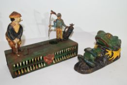 Two novelty metal money boxes, one modelled with golfers, the other modelled as a frog (2)