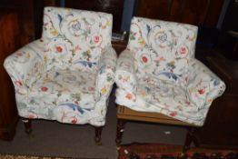Pair of bow back armchairs with mahogany frames and turned front legs with brass casters, fitted
