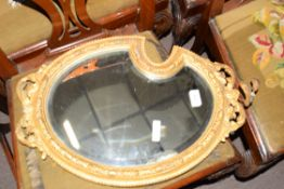 19th century gilt framed mirror with bevelled plate and the frame decorated with foliate detail of