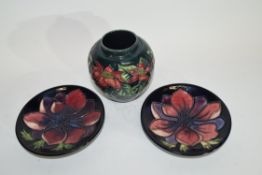 Small modern Moorcroft vase with a floral design on green ground, signed K W to base, together