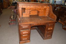 Maple & Co London and Paris, oak tambour roll front twin pedestal desk with fitted interior, the