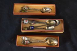 Three small boxes containing a quantity of collectors spoons with enamel finials