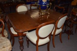 Victorian rectangular mahogany extending dining table raised on fluted legs with casters, together