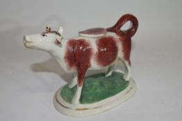 Pottery model of a cow creamer on oval base