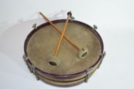 Small circular drum with red stained wooden surround, 31cm wide, together with two drumsticks