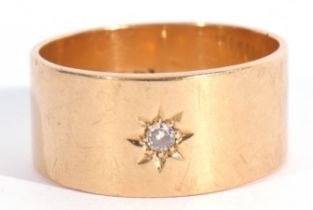 18ct gold and diamond set wide band ring, the plain polished band with a small diamond in a star