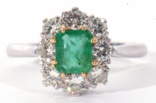Emerald and diamond cluster ring featuring a rectangular step cut emerald, claw set and raised