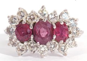 Ruby and diamond cluster ring, a design featuring three graduated oval shaped rubies, surrounded