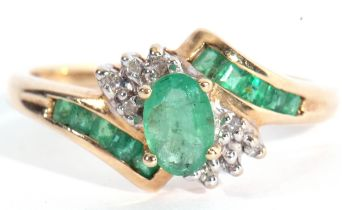 Modern 10K stamped diamond and synthetic emerald cluster ring, centring an oval faceted stone