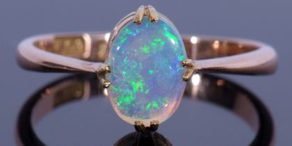 18ct stamped opal ring featuring an oval cabochon opal, cardinal set and raised between tapering