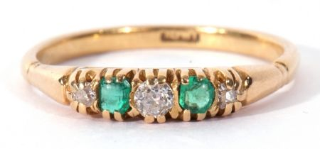 Antique diamond and emerald ring featuring three graduated old cut diamonds and two cushion cut