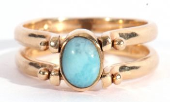Modern reversible ring featuring opposite blue and amber coloured stones, bezel set between hinged