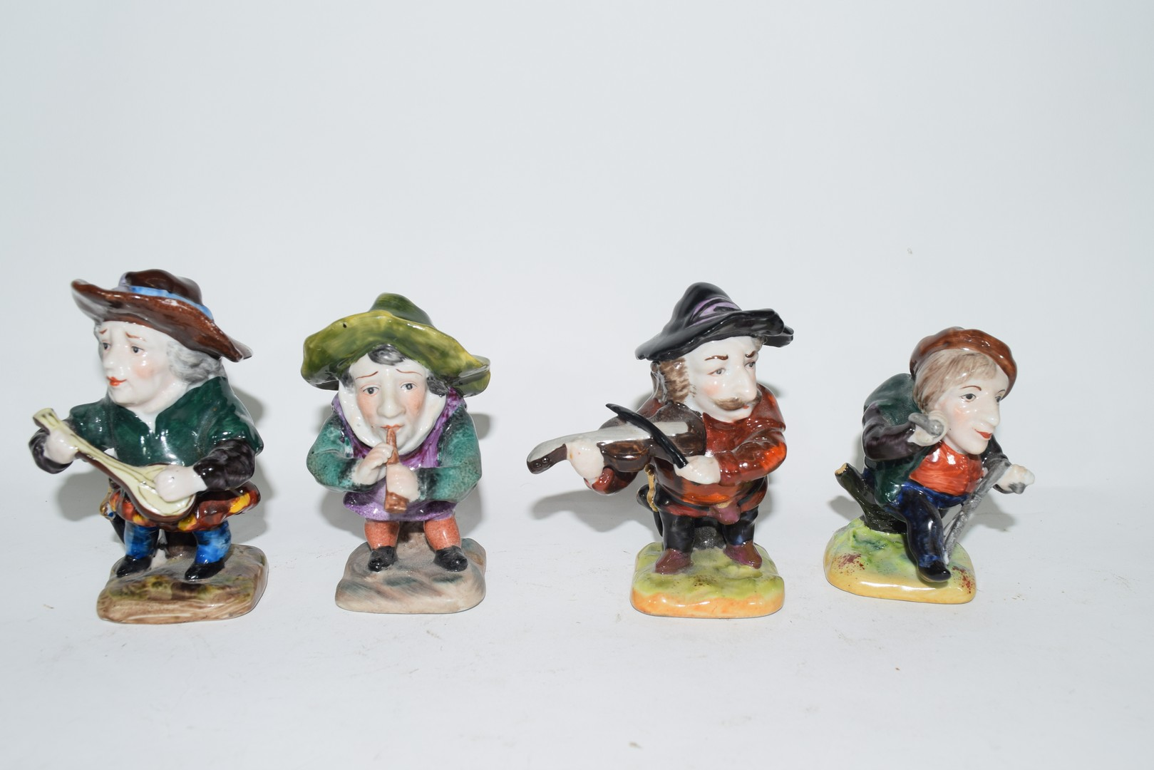 Four 20th century Naples pottery dwarves 9cm in height