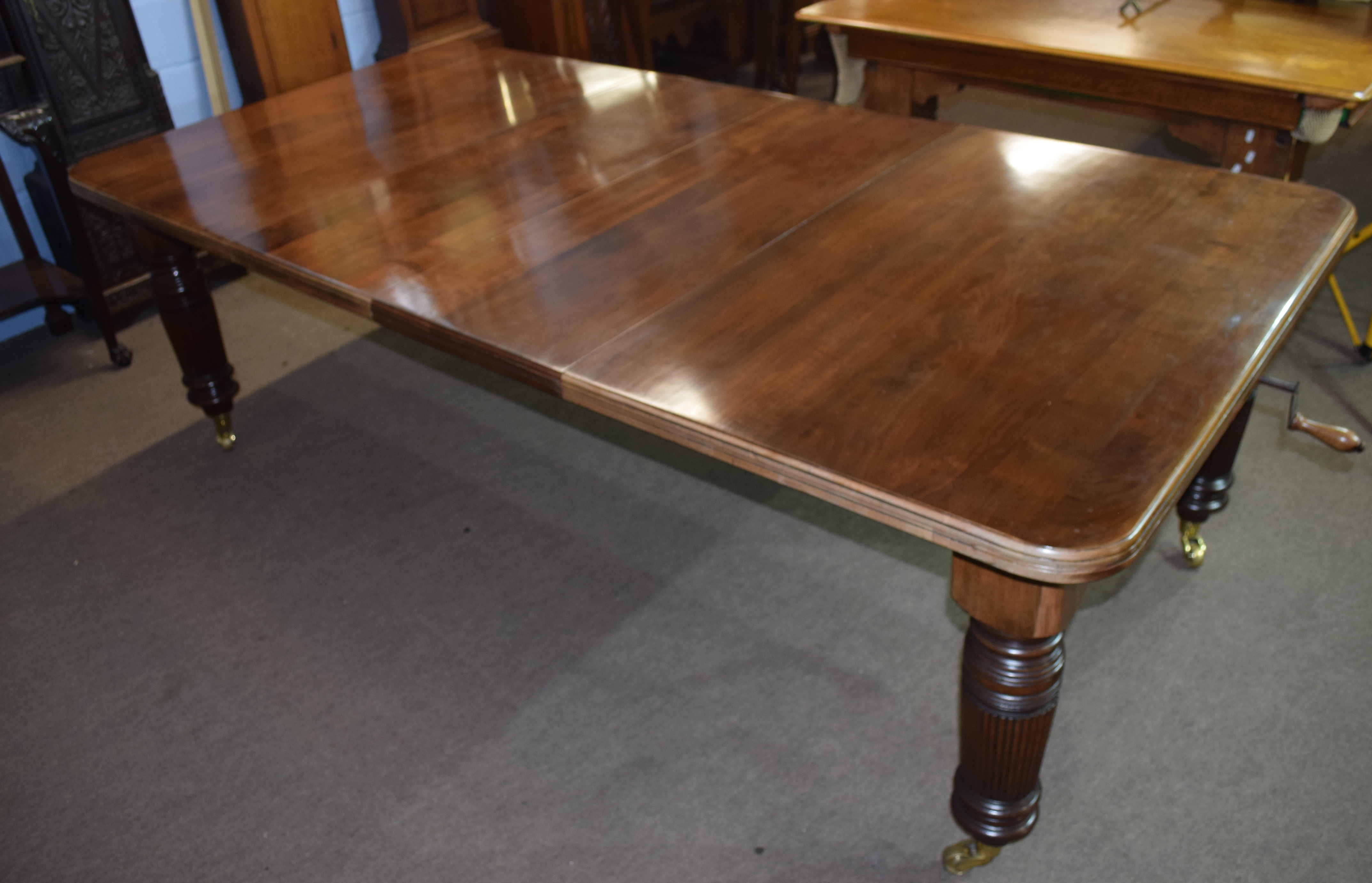 Late Victorian mahogany extending dining table raised on fluted legs and brass casters, 237cm wide - Image 6 of 6