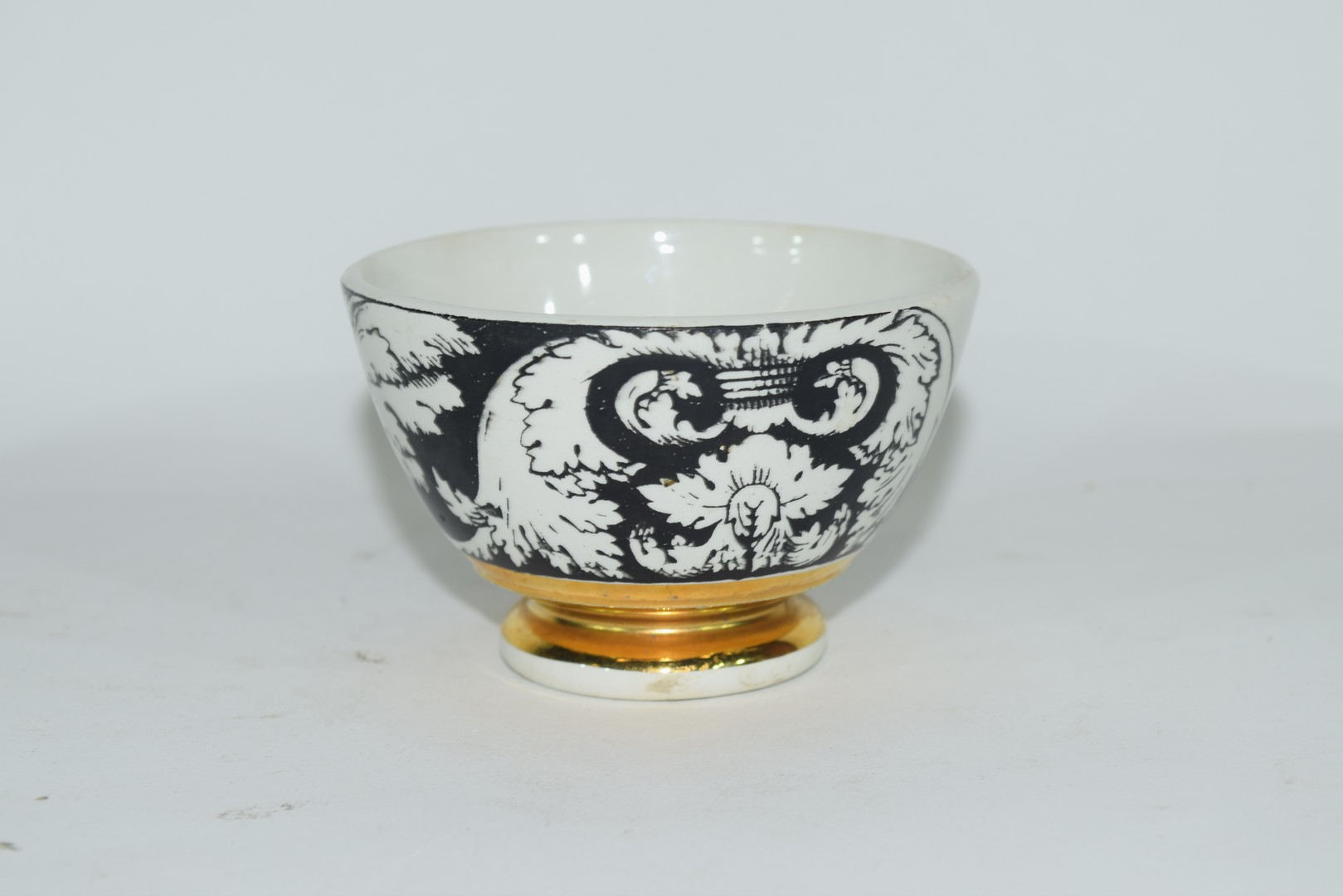 Small bowl decorated in black and white with a design by Fornisetti,