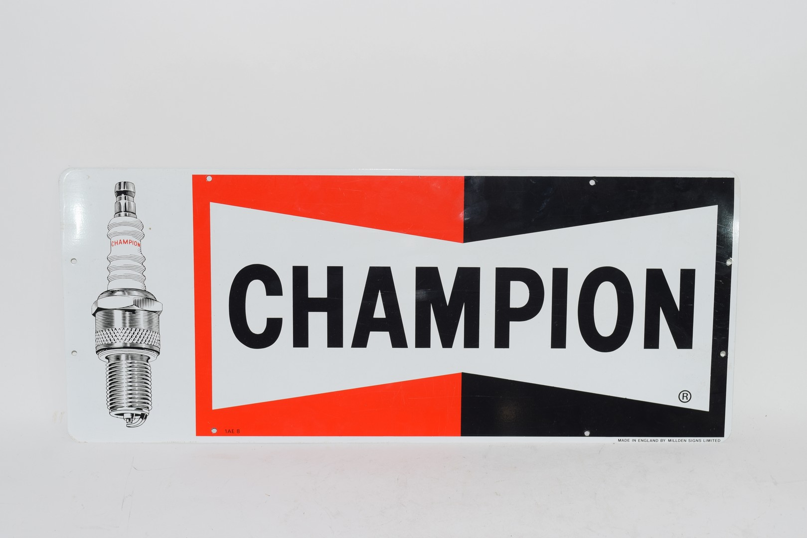 Two metal signs advertising Champion spark plugs