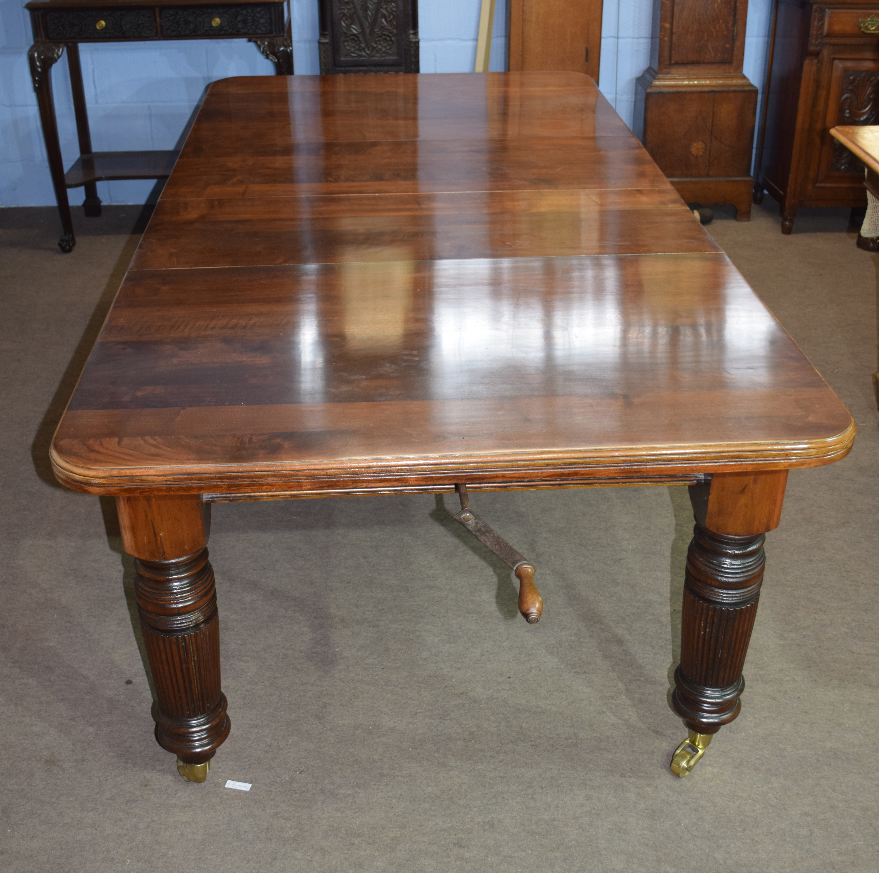 Late Victorian mahogany extending dining table raised on fluted legs and brass casters, 237cm wide - Image 5 of 6