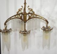 Early 20th century bronze framed four light centre ceiling light fitting, the frame modelled with