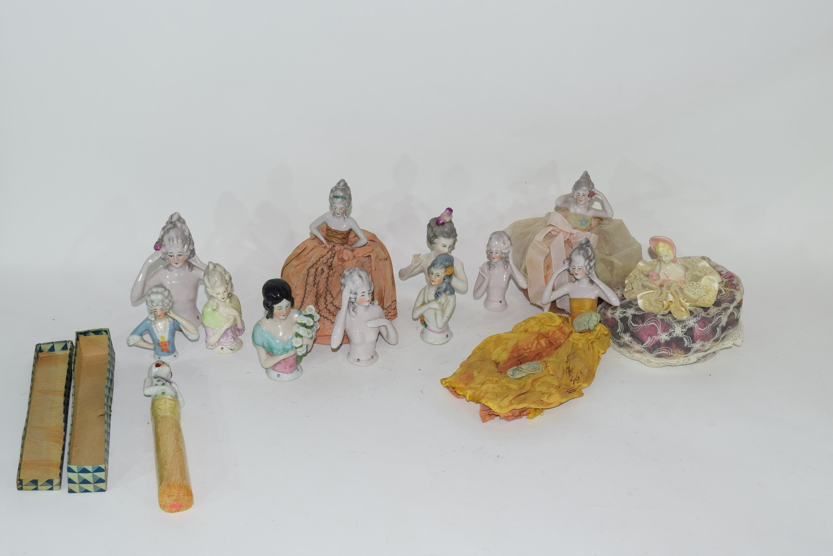 A collection of various continental porcelain pin cushion dolls to include examples in dress, a