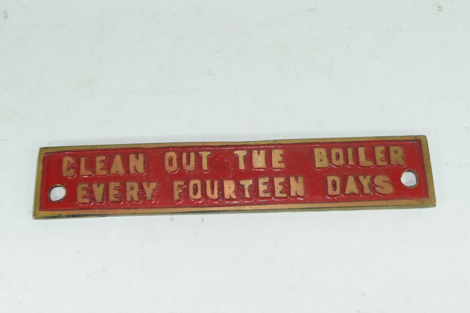 """Small cast brass plaque marked """"Clean out the boiler every 14 days"""""""