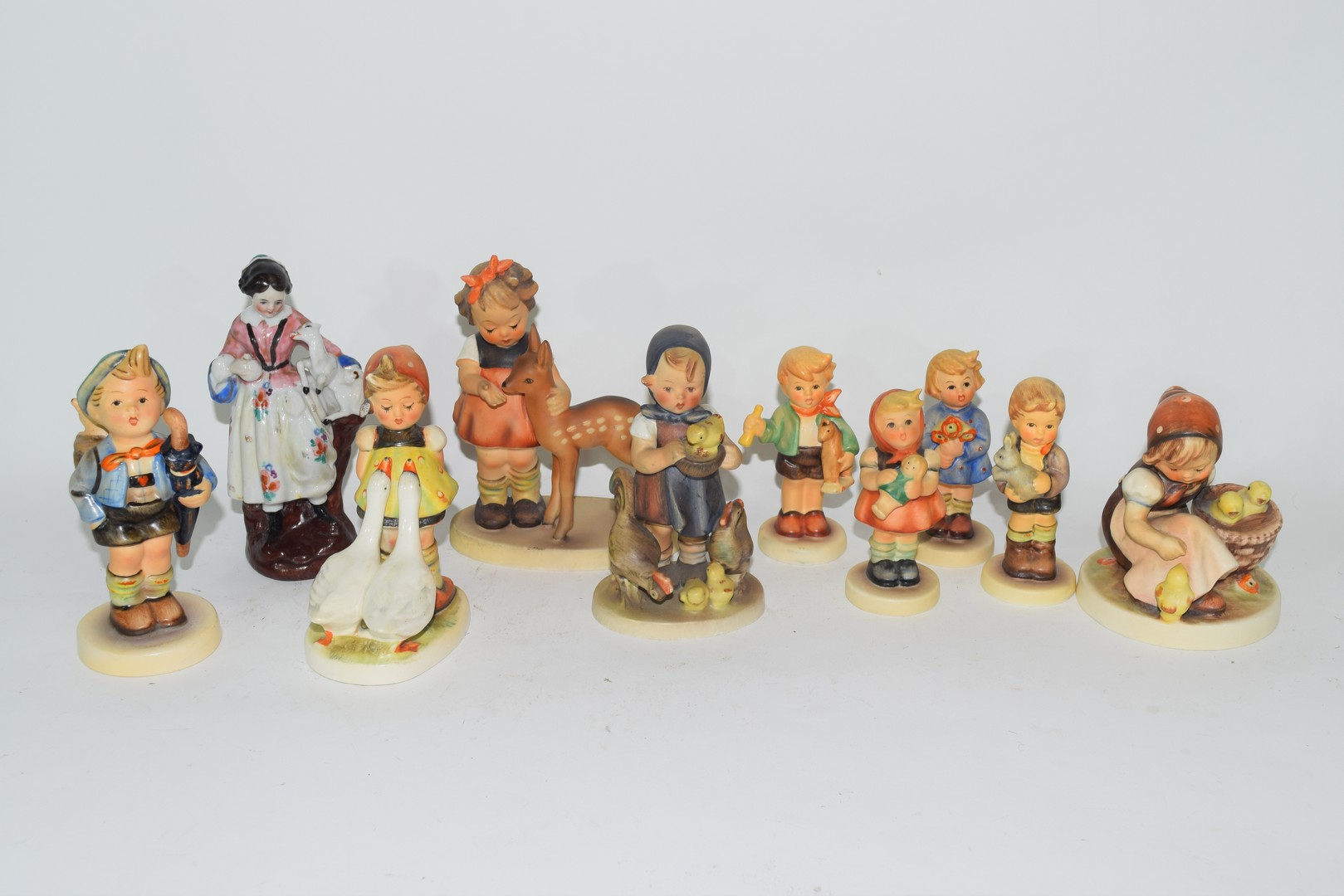 Collection of nine various Goebel/Hummel models of children and a further porcelain figure of a lady