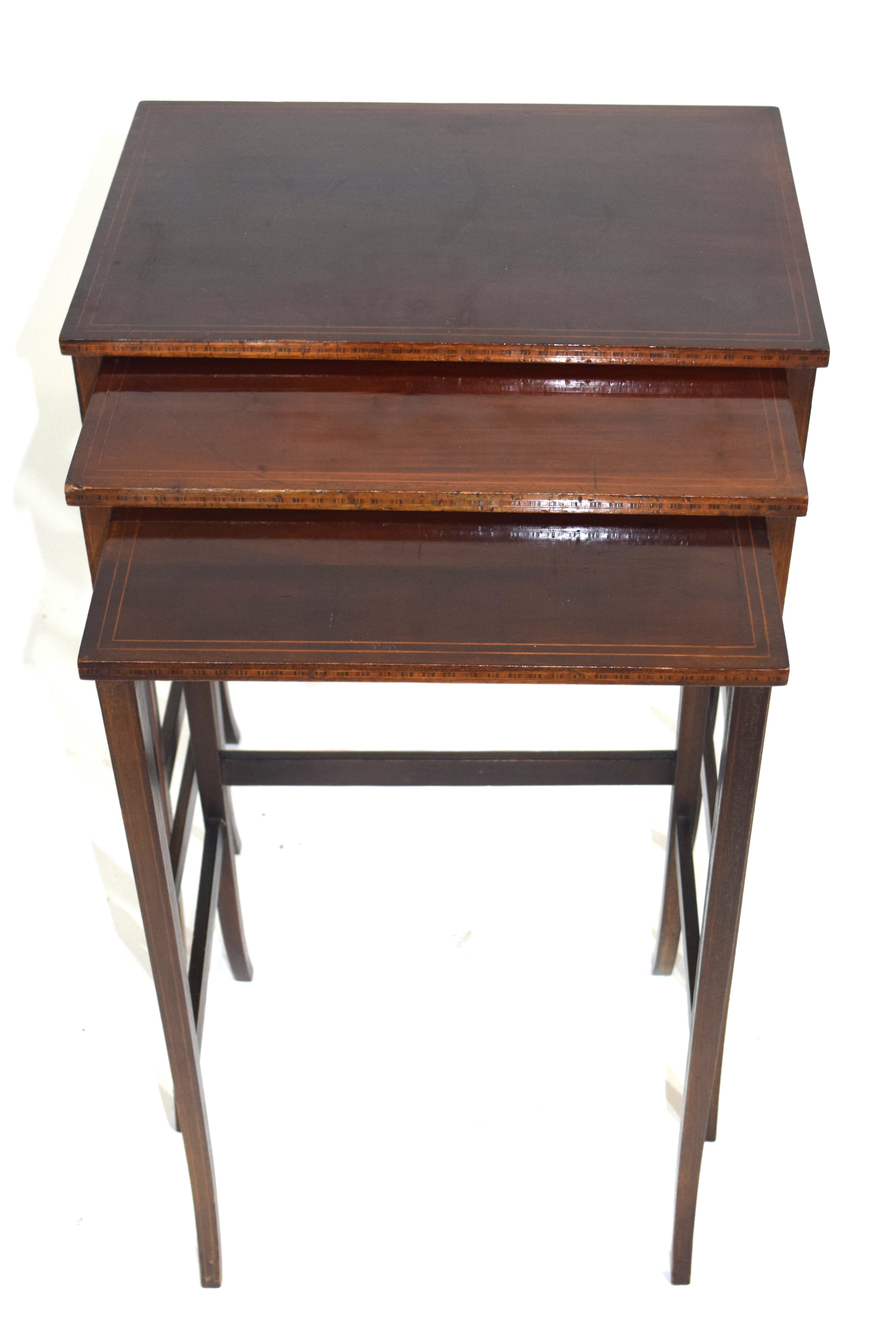 Nest of three Edwardian mahogany and inlaid occasional tables on slender legs, largest 49.5cm wide