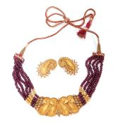 Indian Necklace, a design featuring four articulated textured leaf scroll panels having beaded edges