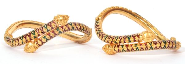 A pair of Indian high-grade yellow metal & enamel serpent bangles, a design featuring two entwined