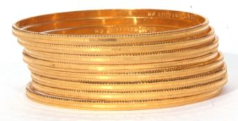 Eight high grade yellow metal bangles each decorated with a steel cut design 80.0gms