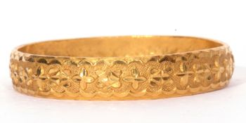A high-grade yellow metal solid cast bangle of circular form, chased and engraved with a