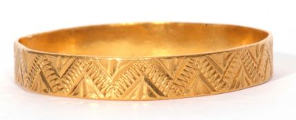 A high-grade yellow metal solid cast bangle, chased & engraved with a continuous geometric design