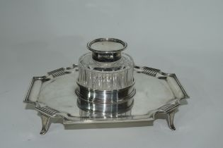 Late Victorian silver ink stand of shaped rectangular form resting on four splayed feet with