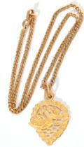 A gold openwork pendant and chain, the pear-shaped pendant chased and engraved with a swan, marked