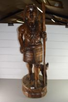 20TH CENTURY CARVED HARDWOOD FIGURE WITH DOG RAISED ON A PLINTH BASE, 90CM HIGH