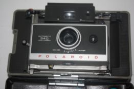 Polaroid automatic 340 land camera together with additional Polaroid land camera and another