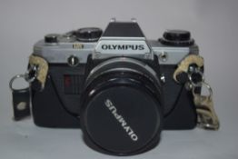 Olympus OM-10 film camera with accessories including strap, flash and Makinon MC35-100mm lens and
