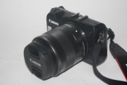 Canon EOS M digital camera together with Canon 18-55mm lens