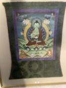 Framed and glazed Tibetan Thangka, mounted within a green and purple fabric mount, size including