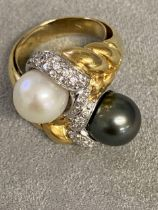An impressive 18ct gold black and white pearl cross over ring, with central band of platinum mounted