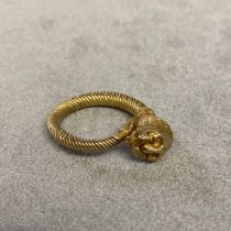 Unmarked yellow metal coil ring with lions head finial, 8.5grams, size M