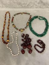 Collection of beaded jewellery, graduated cherry amber strand, uniform double strand of malachite