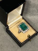A platinum diamond and emerald ladies dress ring, central 5 ct emerald in 8 claw setting, with a