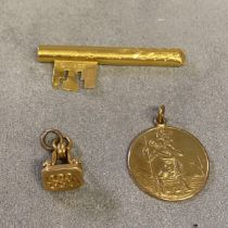 9ct gold St Christopher pendent, 6.1g; unmarked yellow metal key, and an unmarked yellow metal watch