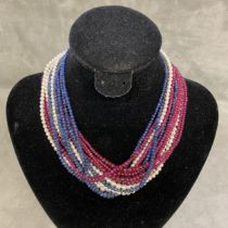 A triple stand necklace of cabochon ruby, sapphires and seed pearls, on a pearl set 14ct white