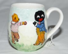 Cricket mug. A small hand painted china mug by Joan Allen featuring two golliwogs and a teddy bear